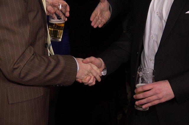 Dva muži držící sklenice, podávající si ruce